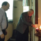 Fr Denis and David Arnold light a candle each in commemoration of some of the Holocausts remembered during the evening.